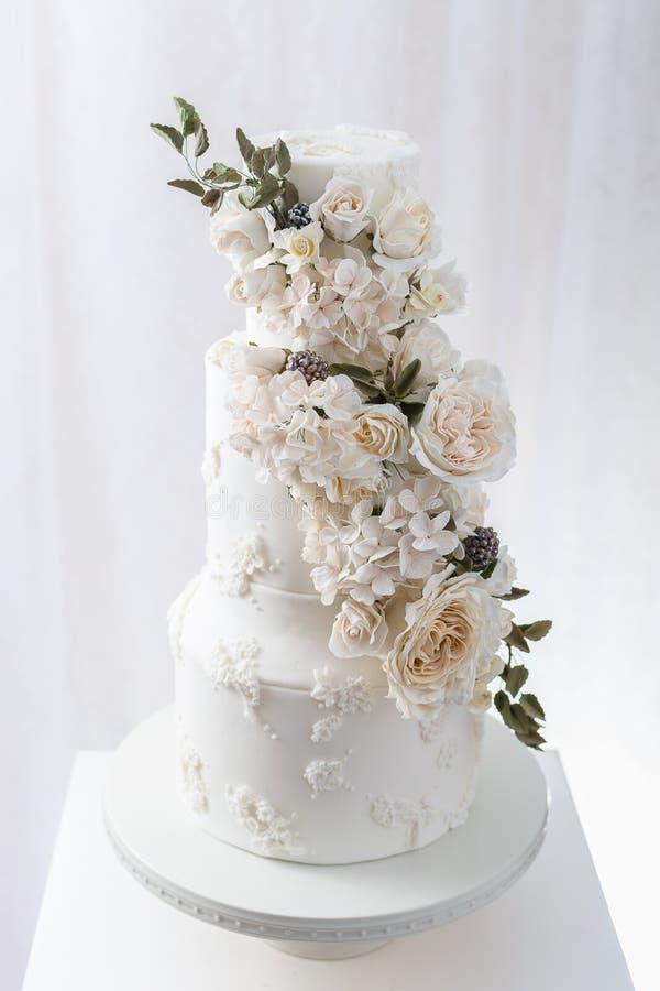 Torta nunziale a file con i fiori commestibili fotografia stock libera da diritti