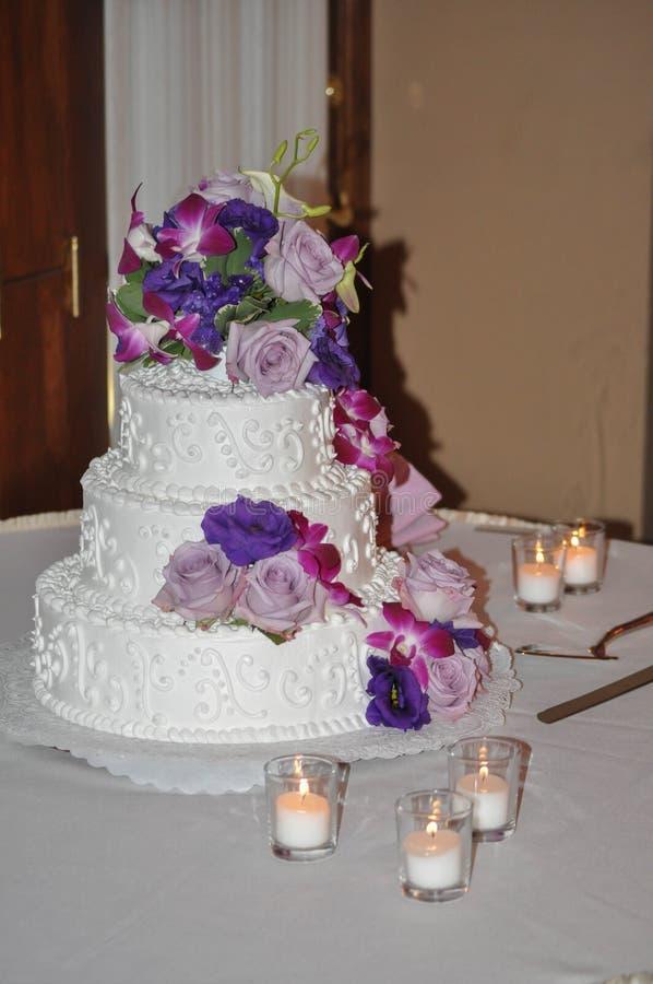 Torta nunziale a file con le candele, le rose ed i fiori immagini stock