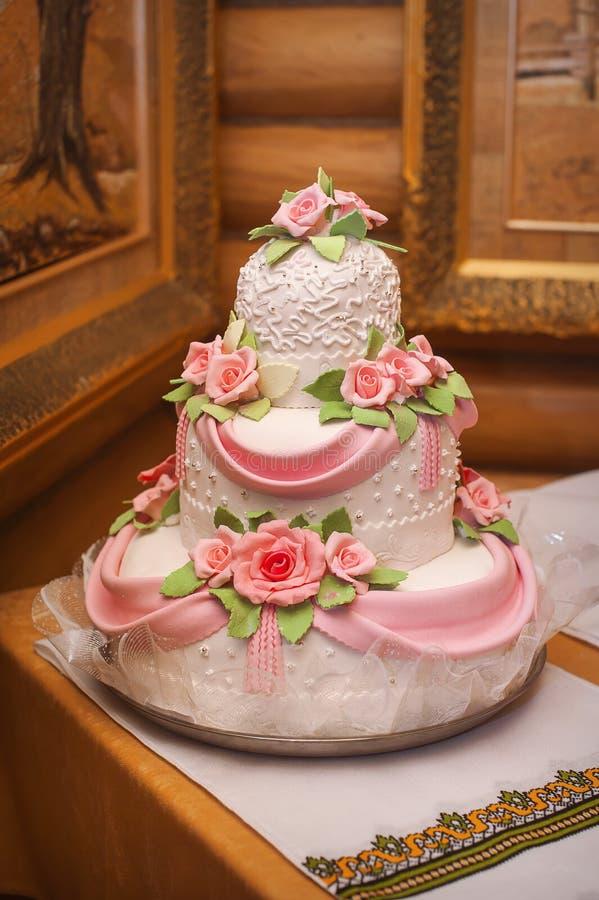 Torta nunziale rosa e bianca con le rose fotografia stock libera da diritti