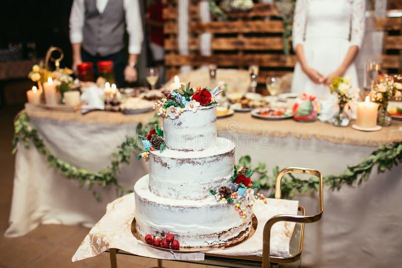 Torta nunziale rustica sul banchetto di nozze con la rosa rossa e l'altra f fotografie stock