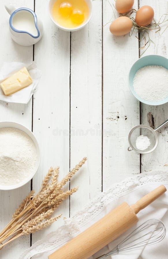Torta que cuece en la cocina rústica - ingredientes de la receta de la pasta en la tabla de madera blanca fotografía de archivo