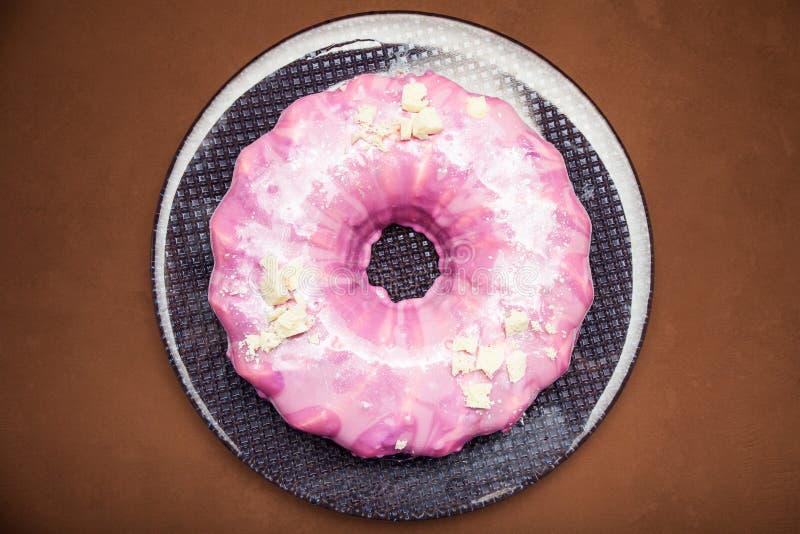 Torta redonda rosada bajo la forma de buñuelo con las rebanadas de chocolate blanco imagen de archivo libre de regalías