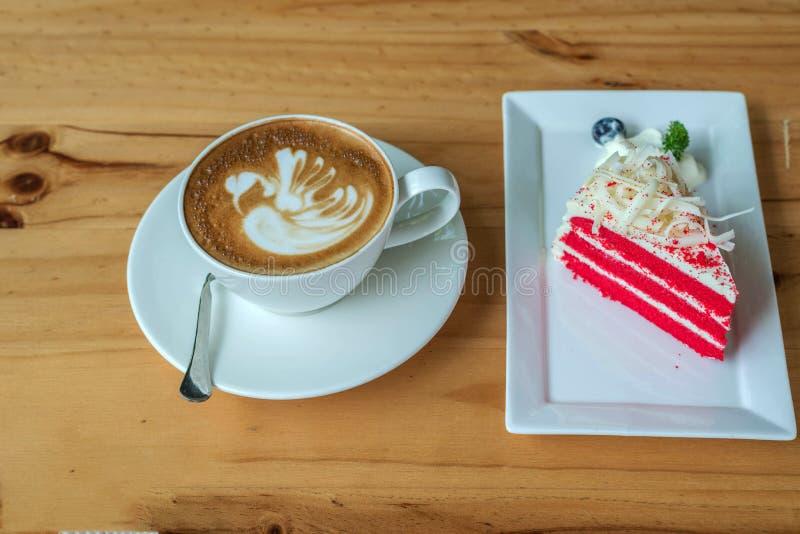 Torta roja del terciopelo en la taza blanca de la placa y de café en la madera fotografía de archivo libre de regalías