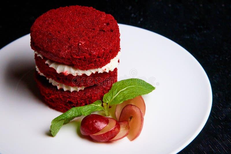 Torta roja del terciopelo y manzana fresca en una placa blanca fotografía de archivo