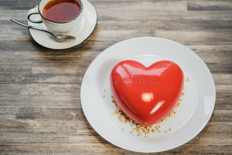Torta roja helada en la forma de un corazón Tabla de Brown y taza de madera de té en el fondo imágenes de archivo libres de regalías