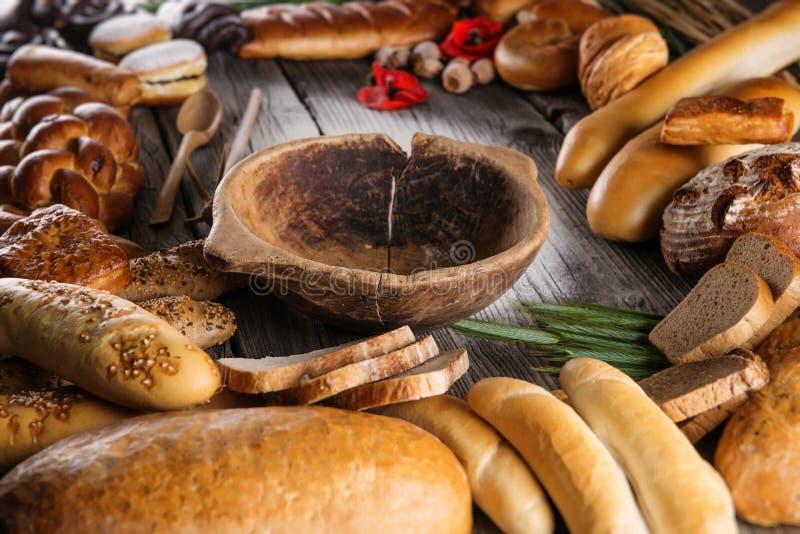 Torta, rollos y panes en la tabla de madera con el cuenco de madera, fondo para la panadería o mercado de la Navidad imagenes de archivo