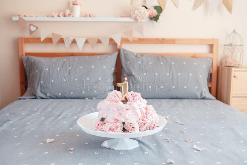 Torta rosada con las flores color de rosa reales naturales grandes y vela en soporte en el dormitorio para el cumpleaños del bebé foto de archivo libre de regalías