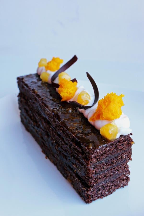 Torta tradicional de Sacher con los pedazos del albaricoque y la decoración anaranjada de la esponja de la microonda fotos de archivo