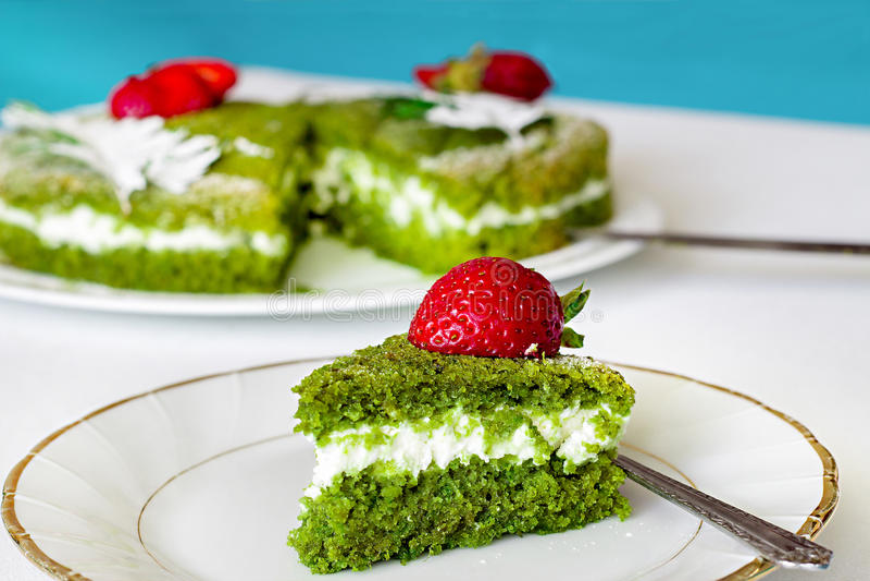 Torta verde de la espinaca con crema y la fresa de la mantequilla en un blanco-g imágenes de archivo libres de regalías