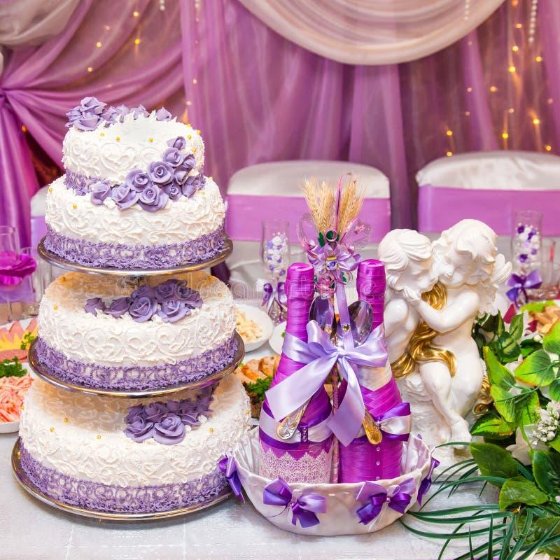 Torta y botellas de vino en una tabla que se casa adornada imagenes de archivo