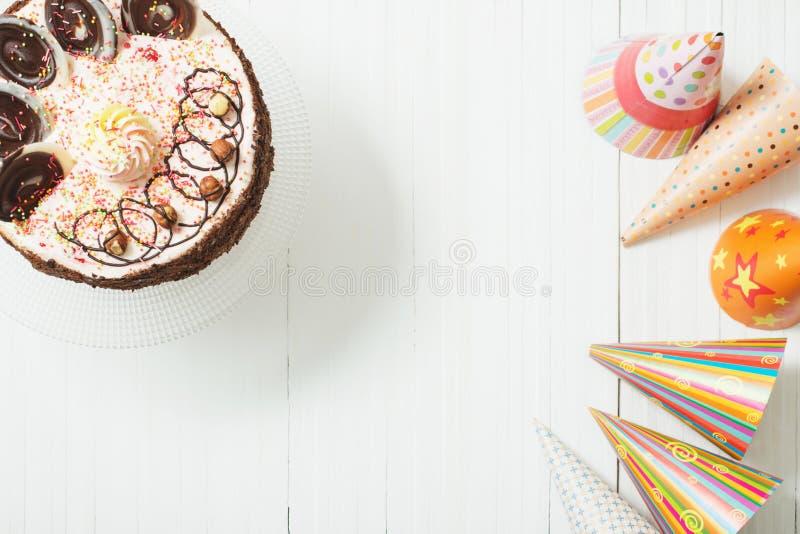 Torta y decoración de cumpleaños en el fondo de madera blanco fotografía de archivo