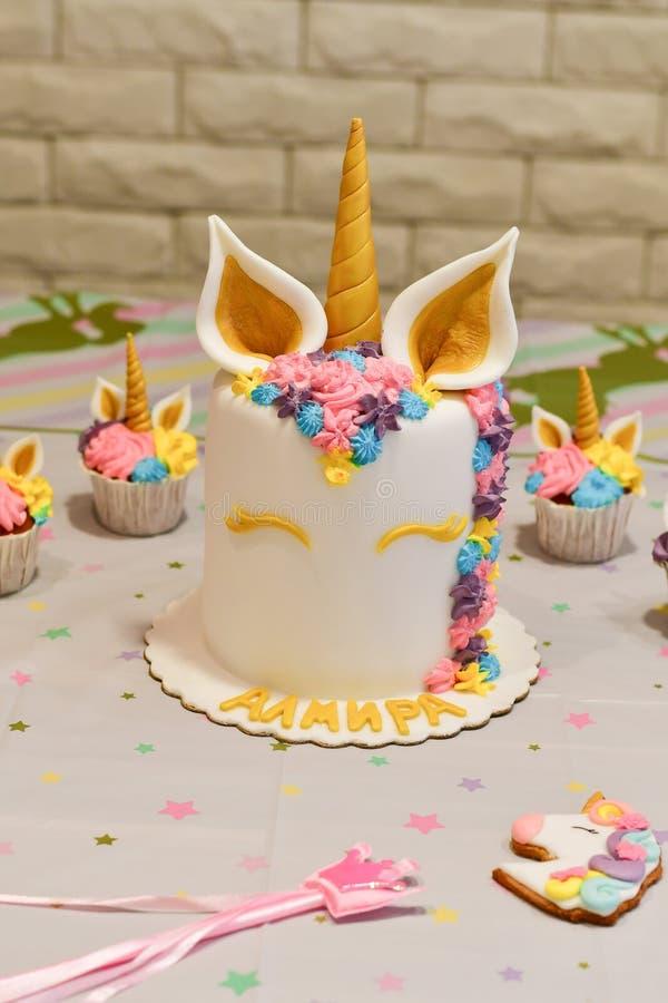 Torta y magdalenas del unicornio para un partido imagen de archivo