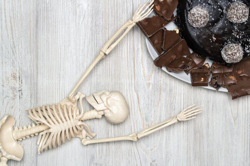 Torta y rebanadas de chocolate en una placa y un esqueleto en una tabla de madera Concepto de muerte de la diabetes fotos de archivo