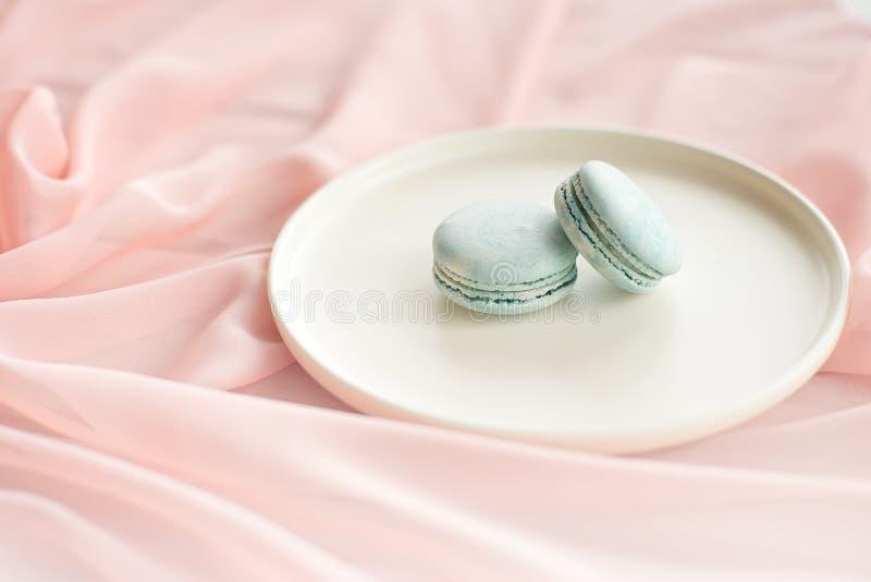 Tortas azules de los macarrones o de los macarrones con las flores rosadas de la materia textil en una placa de cerámica blanca e fotos de archivo libres de regalías