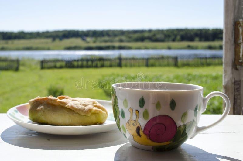 Tortas caseiros deliciosas e um copo do chá no fundo da vila da soleira imagem de stock