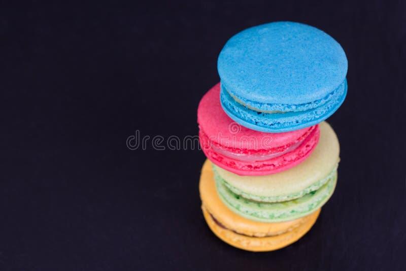 Tortas clasificadas francesas de los macarons en un fondo negro Pequeñas tortas francesas coloridas Visión superior foto de archivo libre de regalías