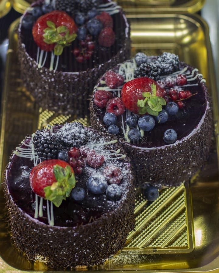 Tortas de chocolate en una ventana de la tienda de pasteles, la torta de chocolate con las bayas, las frambuesas, las zarzamoras  imágenes de archivo libres de regalías