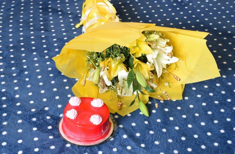 Tortas de cumpleaños deliciosas de la fresa con el ramo envuelto precioso de la flor imagen de archivo libre de regalías