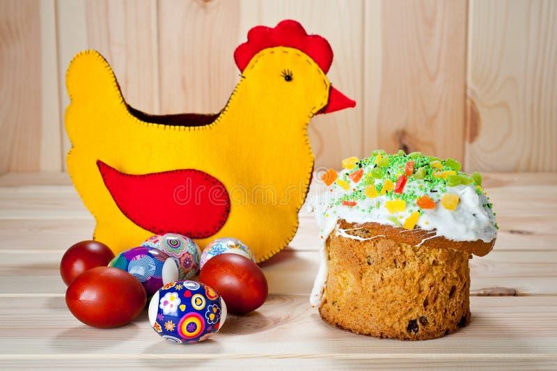 Tortas de Pascua y huevos pintados con el pollo de Pascua en una tabla de madera fotografía de archivo libre de regalías