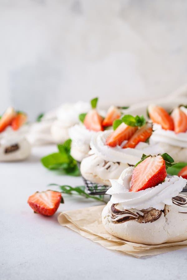 Tortas de Pavlova con crema azotada y bayas frescas del verano imágenes de archivo libres de regalías
