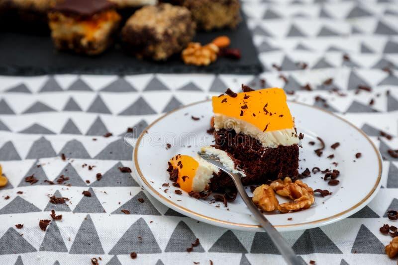 Tortas del chocolate, del caramelo y de las naranjas con el fondo divertido foto de archivo