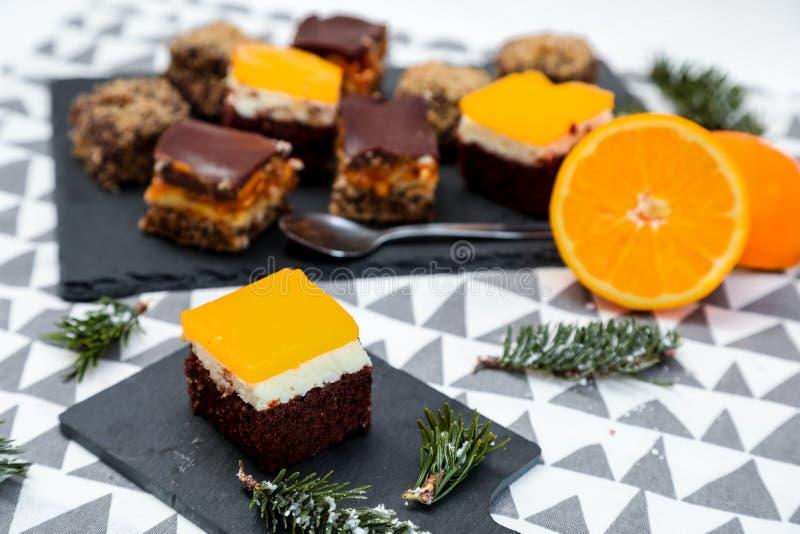 Tortas del chocolate, del caramelo y de las naranjas con el fondo divertido imagen de archivo libre de regalías