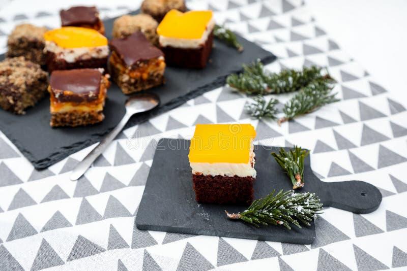 Tortas del chocolate, del caramelo y de las naranjas con el fondo divertido fotografía de archivo