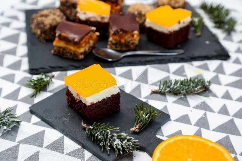 Tortas del chocolate, del caramelo y de las naranjas con el fondo divertido foto de archivo libre de regalías