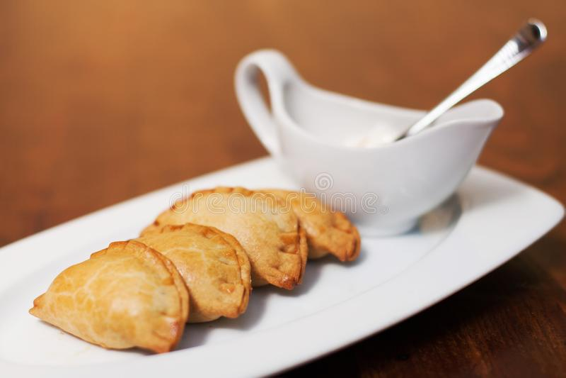 Tortas em uma placa branca com uma caçarola Tapas espanhóis da culinária no fundo marrom, foco seletivo macio foto de stock