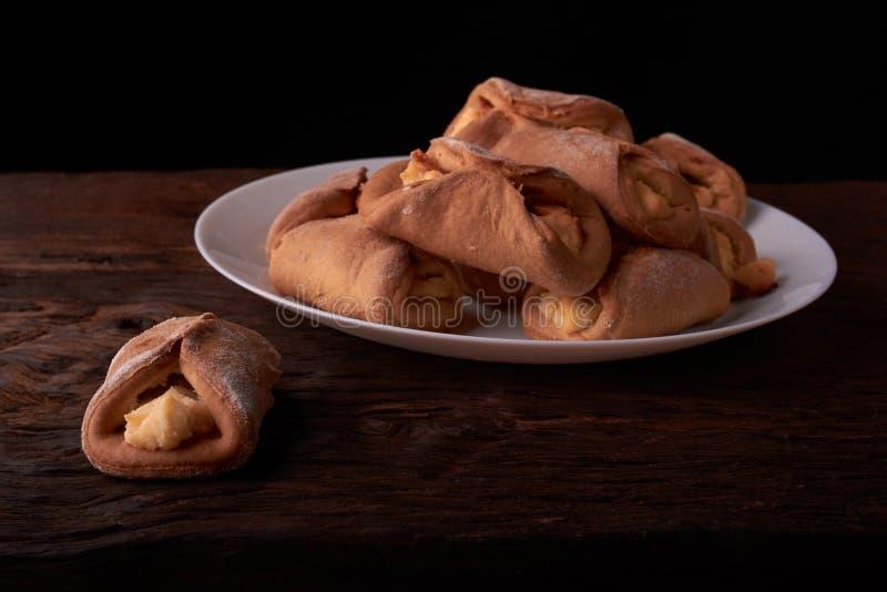 tortas frescas com requeijão de uma massa de fermento em uma mesa de madeira, cozendo com requeijão Conceito da padaria da empres fotografia de stock royalty free