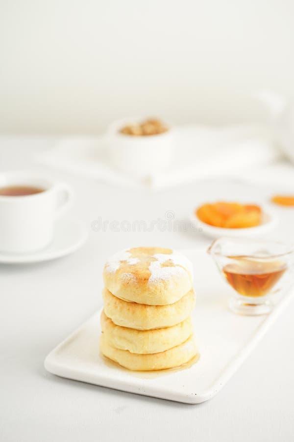Tortas fritas del queso, crepes dulces del queso en la placa blanca en el fondo blanco, vertical Fiesta del té casera fotos de archivo libres de regalías