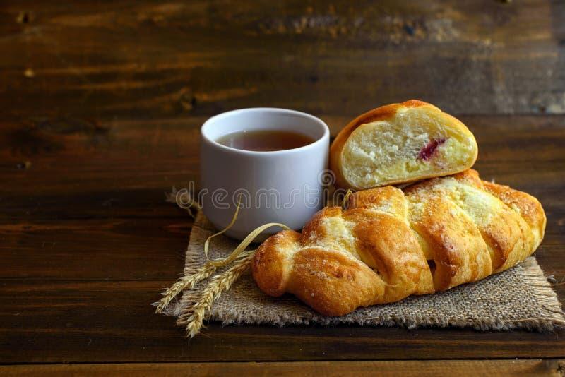 Tortas hechas en casa - pasteles con el queso cremoso y mermelada de fresa y una taza blanca de té en fondo de madera oscuro imagenes de archivo
