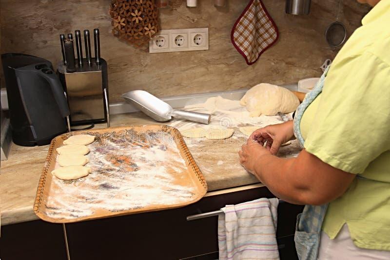 Tortas superiores do cozimento da mulher em sua cozinha home A avó cozinha tortas Alimento cozido Home bolos do molde do omemade  foto de stock royalty free