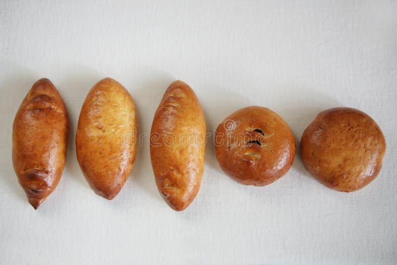 Tortas tradicionais do russo delicioso com o enchimento apresentado em uma linha em um fundo branco imagem de stock