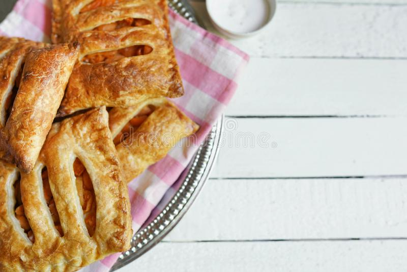 Tortas y pasta de hojaldre hechas en casa con las manzanas y el caramelo en el fondo de madera blanco de la tabla con el espacio  imagen de archivo libre de regalías
