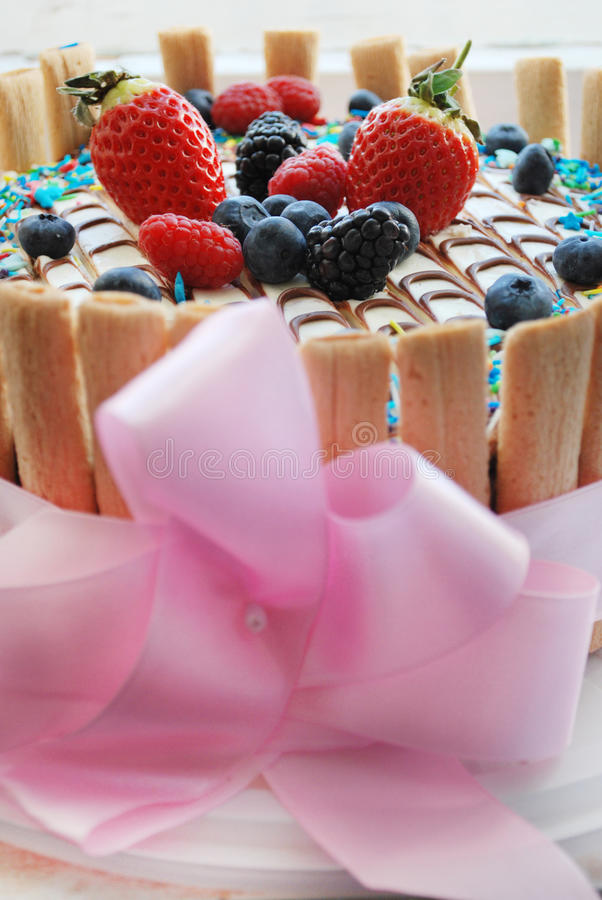 Torte. Birthday cake with berries (strawberries, blueberries, blackberries, raspberries) and is decorated with a pink bow royalty free stock photos