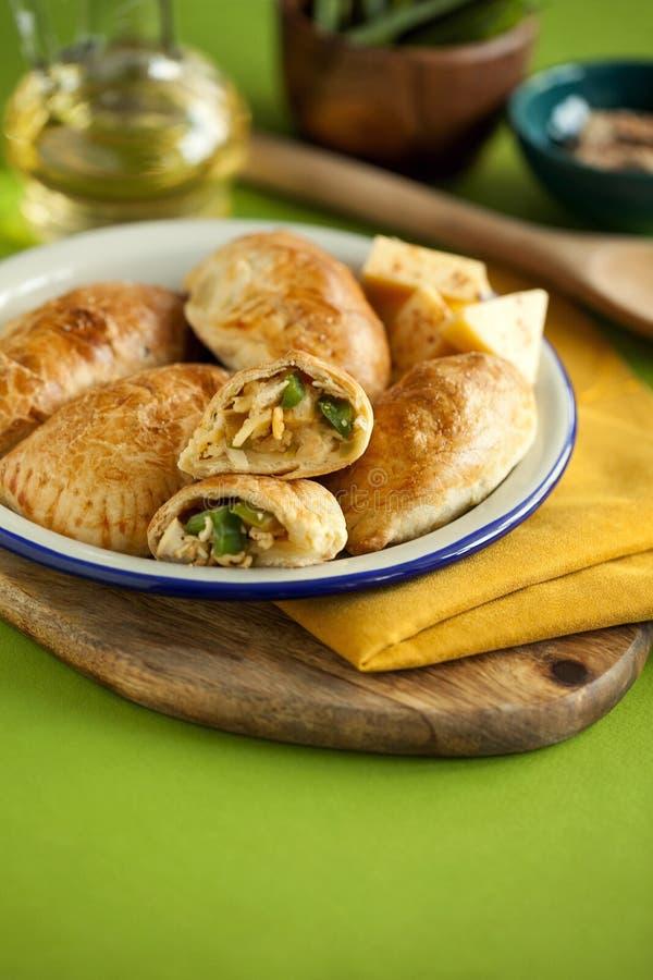 Torte al forno casalinghe della pasta sfoglia farcite con il pollo, il formaggio ed il pepe sul primo piano verde del fondo Spazi fotografia stock libera da diritti