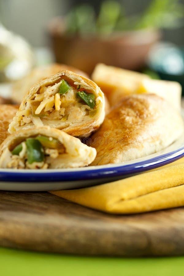 Torte al forno casalinghe saporite della pasta sfoglia farcite con il pollo, il formaggio ed il pepe sul primo piano verde del fo immagine stock