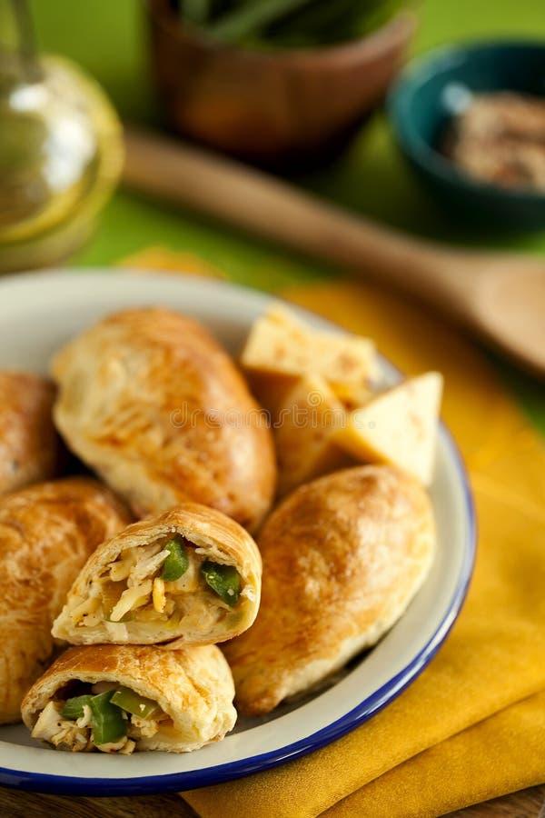 Torte al forno casalinghe saporite della pasta sfoglia farcite con il pollo, il formaggio ed il pepe sul primo piano verde del fo immagini stock libere da diritti
