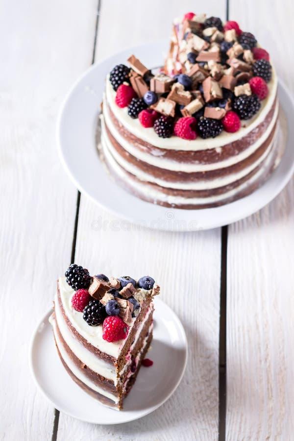 Torte auf weißem Holztisch und eine Scheibe auf Untertasse lizenzfreie stockfotos