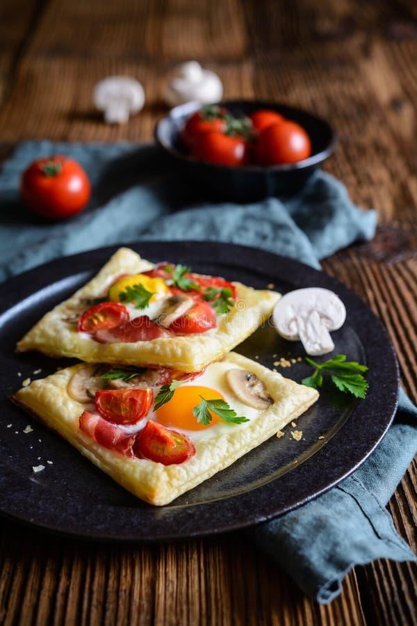 Torte della pasta sfoglia con l'uovo, il bacon, i funghi ed il pomodoro fotografia stock
