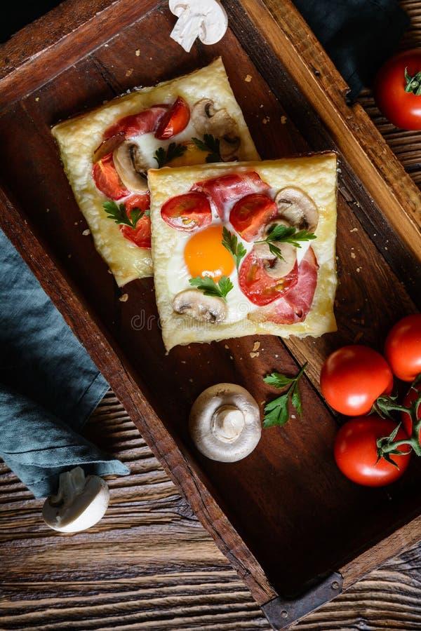 Torte della pasta sfoglia con l'uovo, il bacon, i funghi ed il pomodoro fotografia stock libera da diritti