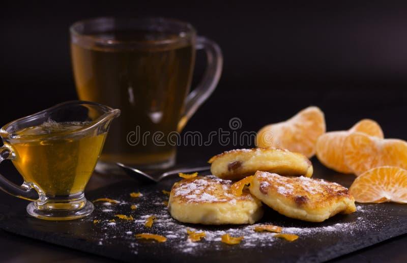 Torte di formaggio con l'uva passa, le patatine fritte del mandarino e lo zucchero in polvere Dopo saranno le fette di mandarino, immagini stock