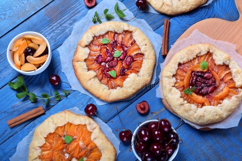 Torte di galette di biscotto al burro con le albicocche, le ciliege e le mele completate con la menta immagini stock