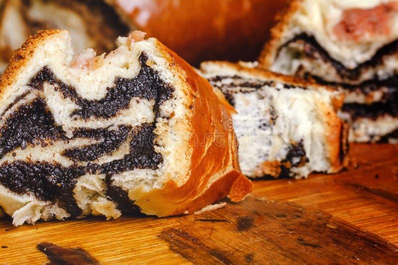 Torte dolci casalinghe al forno calde e fresche, strudel con il seme di papavero che riempie sul bordo di legno immagini stock libere da diritti