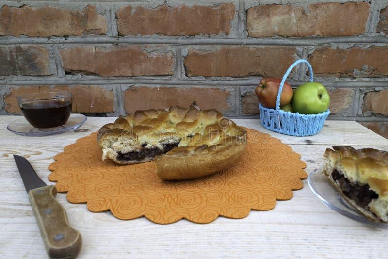 Torte, ein Stück Apfelkuchen mit Kirsche und Walnüssen, eine Tasse Tee, ein Messer und Äpfel in einem Korb auf dem Tisch stockfotografie