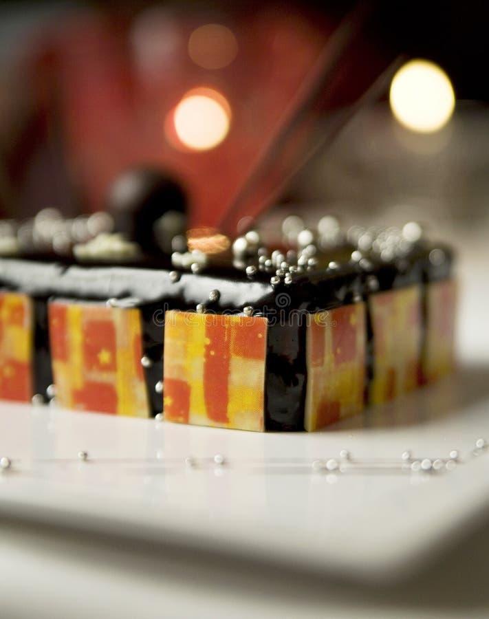 Torte foncé de chocolat avec les truffes main-plongées image stock