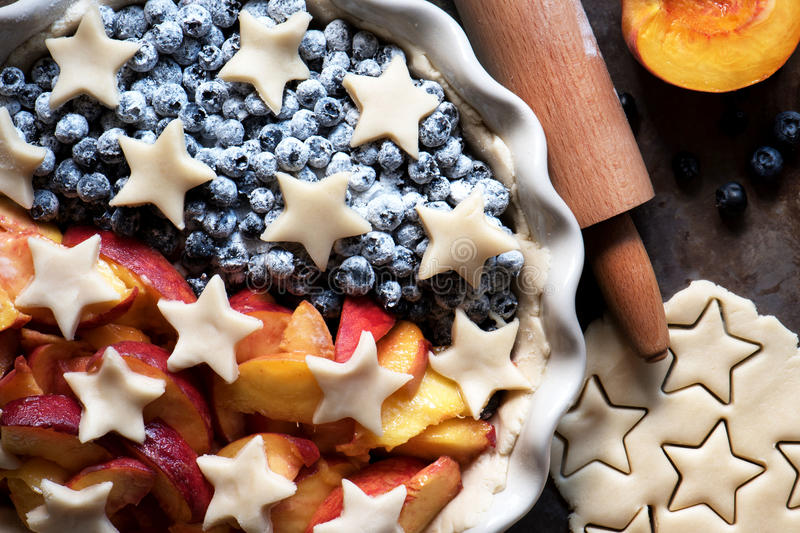 Torte mit frischen Blaubeeren und Pfirsichen, bevor dem Backen stockfotografie
