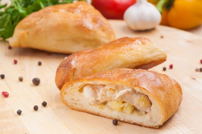 Torte mit Huhn und Kartoffeln auf einem hölzernen Brett Abschluss oben Verziert mit Gemüse und Kräutern stockbild
