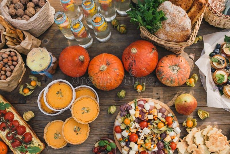 Torte mit Kirschtomaten, Kürbiskuchen, Orange und Papiertüte mit Nüssen stockfotografie
